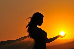 Woman Holding the Sun in the Palm of Her Hand - Photographer unknown